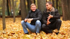 Two men sit on their haunches beside a tree in autumn park and talking Stock Footage