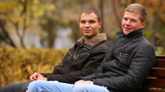 Two young men sitting on a bench in park, one of them talking on the phone Stock Footage