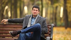 A young man sits in a gray coat on the bench in autumn park Stock Footage