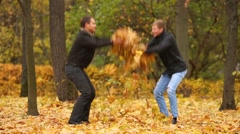Two young men throw up fallen leaves in autumn park Stock Footage