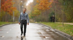 Young man walking on a wet road in the autumn park Stock Footage