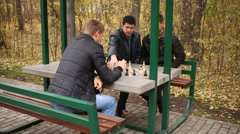 Three friends playing chess in autumn park in a specially equipped place Stock Footage