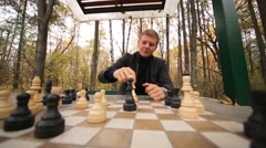 The young man at the table during a game of chess in the park Stock Footage