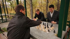 Three young men sitting in the autumn park and playing chess Stock Footage