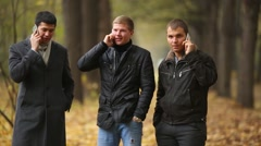 Three young men talking in autumn park on the phone and put them in a pocket Stock Footage