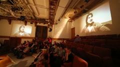 Two screens at walls of auditorium where actress I.Oboldina tells story Stock Footage