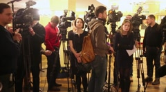 Journalists and cameramen stand in foyer before interviews Stock Footage