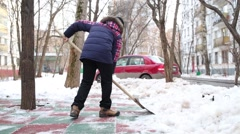 Two boys clean artificial covering of playground with snow shovels. Stock Footage
