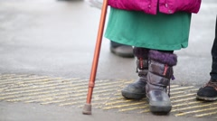 Feet of an old woman and man legs stand at tactile paving for blind men Stock Footage