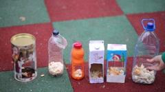 Children hands add bread crumbs into bird feeders standing on covering. Stock Footage