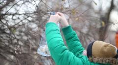 Boy in green jacket hangs big plastic bird feeder on bush branch. Stock Footage