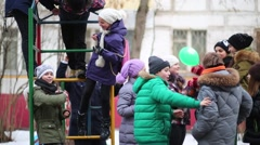 Ten children relax and play at playground on winter day. Stock Footage