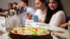 Round cake on table and group of children at tea party. Stock Footage