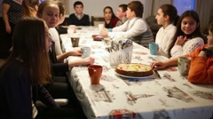 Group of eleven children sits at table during tea party. Stock Footage