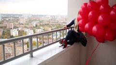 Young woman with a long hair is sitting on balcony and holding balloons. Stock Footage