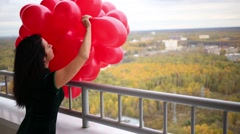 Young woman in black dress is holding many balloons and throwing away one. Stock Footage