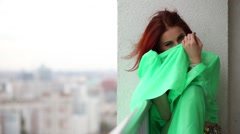 Ginger woman is hiding face behind fabric and sitting on the balcony. Stock Footage