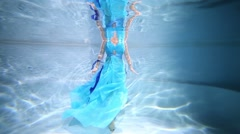 Beautiful young woman is diving under water in blue long dress. Stock Footage