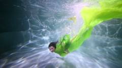 Beautiful woman in green dress is swimming underwater at the pool. Stock Footage
