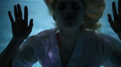 Young blond woman in white dress is swimming underwater. Stock Footage