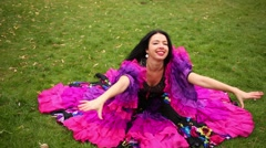 Young gipsy woman is sitting on a lawn and whirling breast around herself. Stock Footage