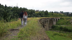 A couple walks along the old viaduct in the mountains Stock Footage