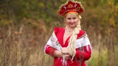 Beauty woman in traditional russian clothes is standing with kerchief. Stock Footage