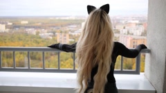 Beauty woman with cats ears is standing on the balcony, back view. Stock Footage
