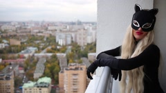 Woman in a black cats mask is standing and scratching air on the balcony. Stock Footage