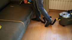 Man is cleaning a dark sofa by the vacuum cleaner. Stock Footage