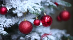 Man is touching red balls which hanging on the artificial fir Stock Footage