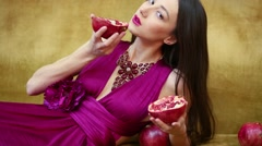 Beautiful girl is laying on the sofa and holding cut pomegranate. Stock Footage