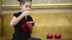 Little beautiful girl is sitting on the sofa and eating pomegranate. Stock Footage