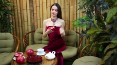 Beautiful girl in dress is filling cup of tea, sitting on sofa near table Stock Footage