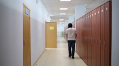 One man is walking on the corridor and talking by phone. Stock Footage