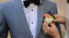 Close up of bride's hand putting the boutonniere flower on a groom's jacket Stock Footage