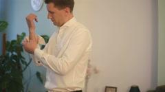 Handsome groom preparing for wedding day. Elegant man wearing cufflinks indoor Stock Footage