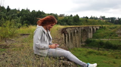 The girl writes sms sitting near the old viaduct in the mountains Stock Footage