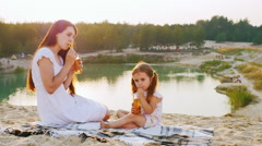 Mum with a daughter three years relaxing on the beach by the lake, drink juice Stock Footage