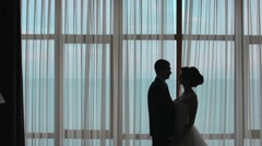 Silhouettes of honeymooners standing next to the window Stock Footage