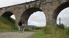 Happy couple walking along the road under the old viaduct Stock Footage
