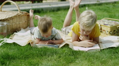 Children using tablet and reading a book Stock Footage