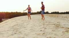 Girl playing with his parents, runs them through the sand on the beach Stock Footage