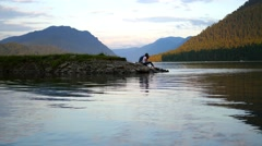 Love couple sitting on river at sunset Stock Footage