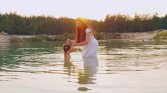 Games with children. Mother and daughter play in the water in the river Stock Footage