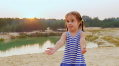 Sweet girl of three years playing ball, catching a ball on the beach Stock Footage