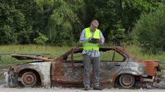 Inspector writing near the car wreck on road - stock footage