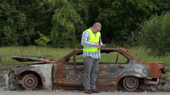 Inspector using tablet PC near the car wreck on road - stock footage