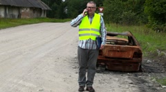 Inspector walking near the car wreck and talking on smart phone - stock footage