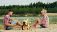 Friends of a man and a woman are sitting around the campfire, roast marshmallows Stock Footage